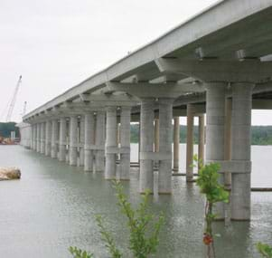 Photo shows a row of concrete columns and beams that compose a bridge crossing a body of water.