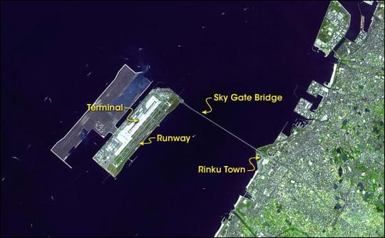 Aerial satellite image shows urban shoreline, blue bay waters, and long bridge connecting shore to a rectangular island containing airport terminal and runways.