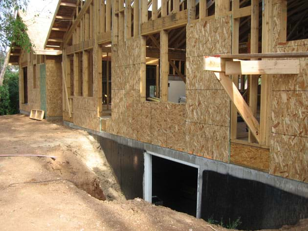 Photo shows an unfinished wood-framed one-story house, with some of its concrete foundation (basement walls) exposed (not backfilled).