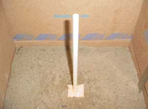 Photo shows the block of wood at the end of a dowel partially submerged in the top soil layer in a cardboard box.