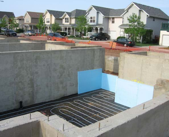 Photo shows a series of unfinished concrete walls that form basements for a new neighborhood.