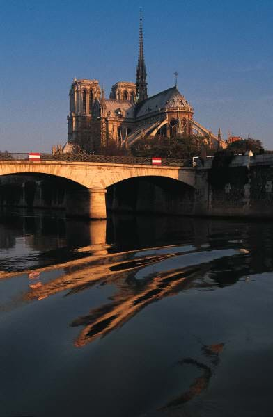 A graceful multi-arched bridge provides access to an island with a cathedral.