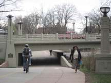 Photo shows bikers and walkers going under a bridge and cars traveling over a bridge.