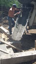 Photo shows concrete pouring down a trough.