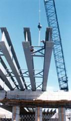 Photo shows a crane moving huge steel I-beams.