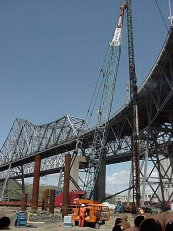 Photo shows a crane lifting a steel truss from the ground to a bridge deck.