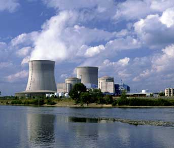 A photograph of a nuclear power plant. Shown is an industrial-looking plant with two large concrete stacks with plumes of steam escaping. The plant sits on the shore of a body of water, and many buildings surround the two stacks.