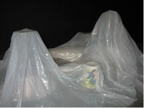 A photograph shows a sheet of white plastic draped over many objects, looking like a hilly terrain.