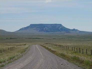 A photograph shows a dirt road leading towards a wide, flat-topped mountain in the distance.