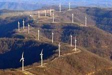 Photograph of 18 wind turbines located on a mountain ridge.