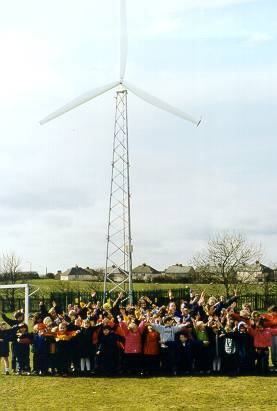 A photograph shows large group of school children standing in front of a tall, three-blade wind turbine.
