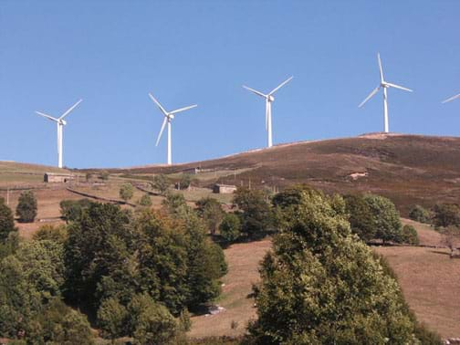 Landscape photo shows four, white, electricity-generating wind turbines on a hillside.