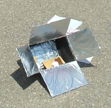 Photo shows a box with flaps covered in foil, and chocolate, marshmallow and graham cracker inside the box.