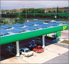 Photo of shiny, blue panels covering the flat roof of a gas station canopy.