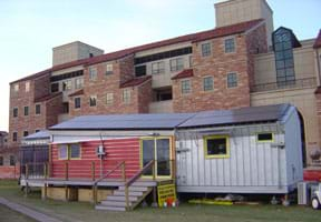 Photograph of a modern mobile-home-size structure in front of a huge university building.