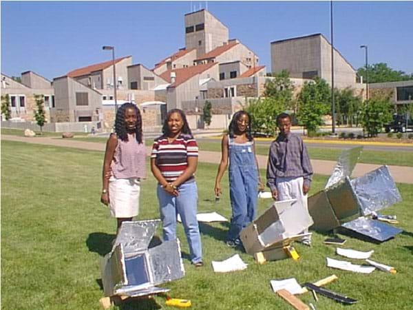 Four teens and three shiny, box-type solar ovens.