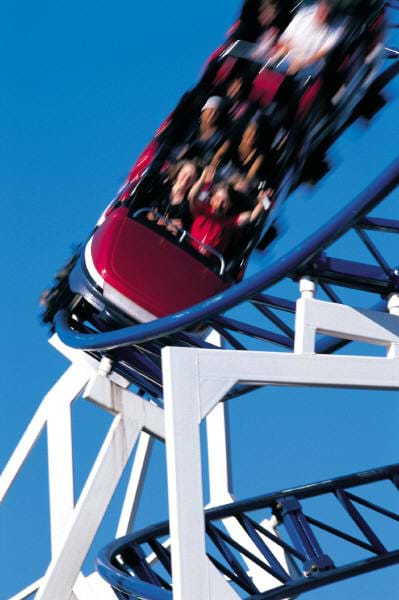 Photograph of people having fun riding on a speeding rollercoaster.