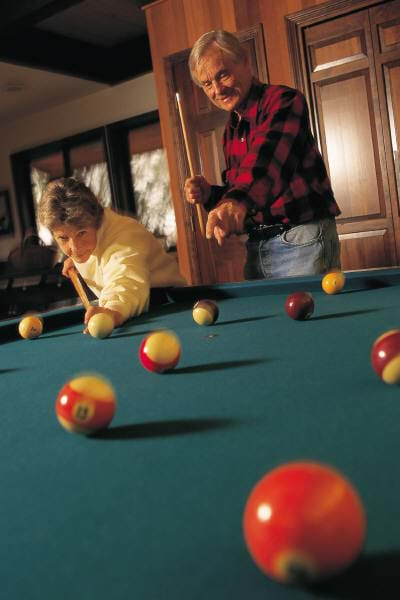 A photograph of a man and woman playing billiards, showing a scattering of balls across the pool table playing surface.