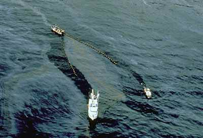 An arial photograph shows two boats dragging a net through the ocean waters, skimming oil off the water surface.