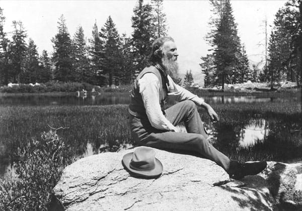 A portrait of John Muir, facing right, seated on a rock with lake and trees in background.