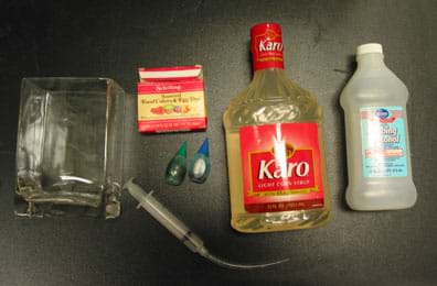 Bottles of corn syrup and alcohol, syringe with tube connected, box of liquid food coloring in small plastic squeeze bottles, square glass container.