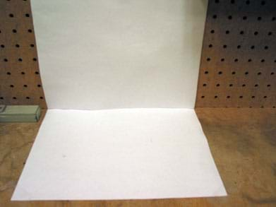 Photo shows two pieces of white paper affixed perpendicularly, to a wall and a table top.