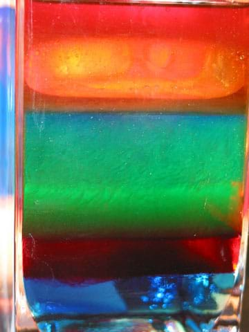 Photo shows a drinking glass with indistinct layers of blue, dark red, green, blue and orange fluids.