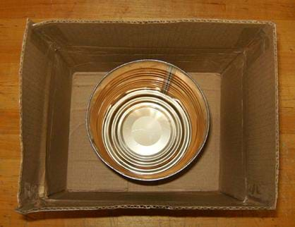 A photo looking down into a cardboard box with an open metal coffee can placed at the bottom.