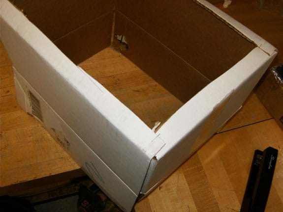 Photo shows the bottom of a cardboard box with the cardboard cut away except for a one-inch edge on the four sides.