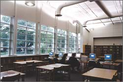 In a classroom with tables, chairs, desks and computers, light comes in through large windows and a round ceiling opening.
