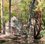 A photograph shows a large wooden water wheel near a stone structure and creek.