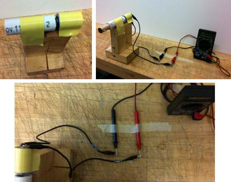 Three photos: (top left ) A short piece of white PVC pipe and a cylindrical DC motor are duct taped to the top of a wooden platform made from two pieces of 2x4 wood attached perpendicularly. (top right) Alligator clip wires connect the motor in the set-up in the top left photo to the black and red multimeter probe leads. (bottom) An overhead view shows how the wires connect the motor to the multimeter.