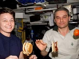 Photo shows two astronauts eating floating sandwiches and fruit aboard the International Space Station (ISS).