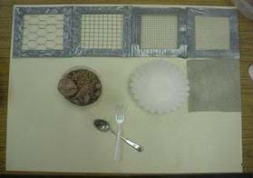 "A photograph showing the activity ""filters."" From left to right are different-sized screening with large holes to small holes. Also shown is poultry netting, a coffee filter, a container of pebbles and a fork and spoon."