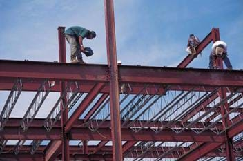 A photograph of I-beams being installed for a structure that is under construction. Three construction workers are standing on the beams working.