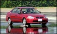 Photograph of a red sedan stopping on a wet road surface, showing a splash of water below the front wheels.