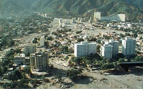 Aerial photo showing sediment pooling around roads, buildings and skyscrapers in a valley and alluvial fan below mountains.
