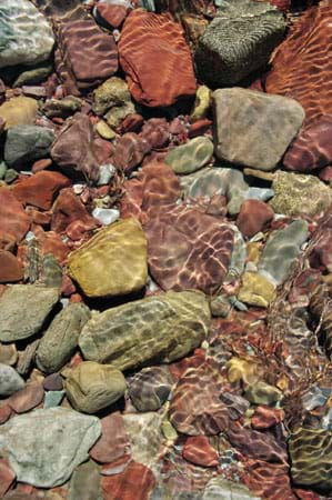 Photo shows different colored rocks through the clear water of a stream.