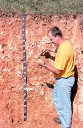 Photo shows a man standing next to a cut-away section of soil as tall as he is, with an attached 76-inch (193-cm) measuring tape, and a short amount of grass and top soil above a deep, reddish-colored bedrock layer.
