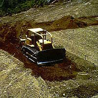 Photograph of a bulldozer pushing piles of soil.