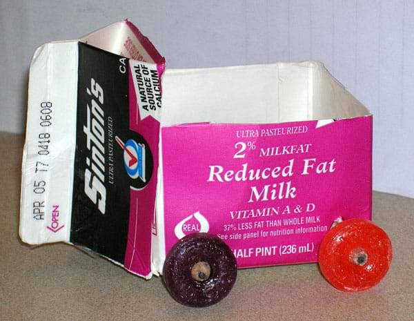 A photograph shows a little vehicle composed of a cut-open milk carton as the cart body with pencil axles and white lifesaver-shaped candy wheels.