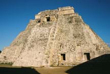 Photo shows a weathered, pyramid-shaped stone structure.