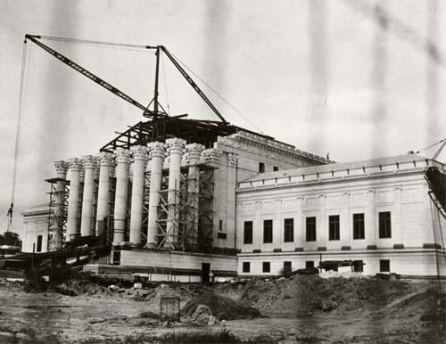 Photograph of a crane lifting materials onto a building under construction.