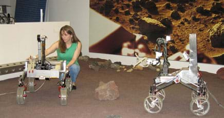 A woman stoops to make an adjustment on one of a pair of four-wheeled metal robots, about the size of large tricycles, in a large indoor sandbox.