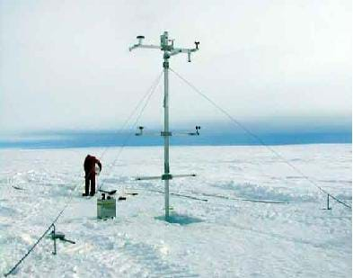 Photo shows a person in an endless snowy field setting up equipment near a 20-ft tower with wires and attachments.