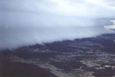 Photo shows bank of very thick, layered white clouds above a town.