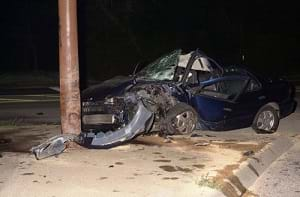 A car crashing into a telephone pole, showing the front end of the car crumpled.