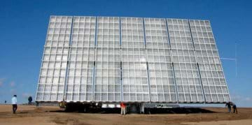 Photo shows a huge panel propped up and facing the sun in an open field. Panel is made of white and clear plastic in sliver metal grids. Panel looks very large next to the men standing near it—maybe 15 meters wide x 12 meters tall.