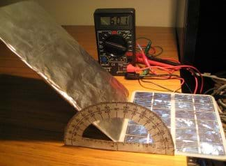 Photo shows a small photovoltaic panel with reflector panel made of foil-wrapped cardboard, hooked with wires to a multimeter.