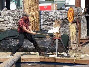 A lumberjack with an axe splitting wood.